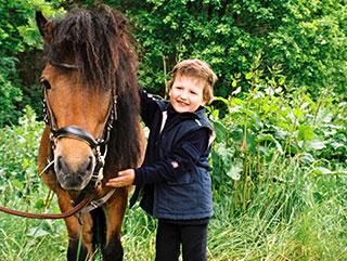 Ein kleiner Junge steht neben einem braunen Pony während des Urlaubs auf dem Landhotel Pferdeschulze