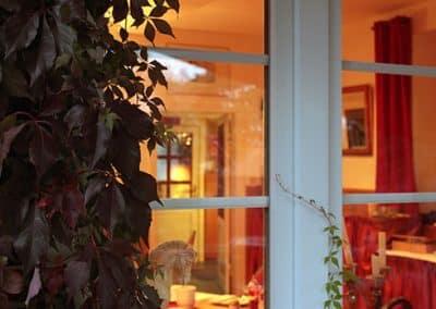 Blick durch ein Fenster in ein Landhotel