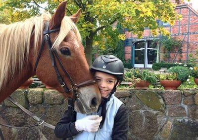 Ein Kind mit Reiterhelm hält sein braunes Pferd mit weißer Mähne fest, während es einen Tag auf dem Reiterhof Pferdeschulze verbringt