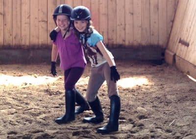 Zwei Mädchen stehen umarmt mit ihrem Reiterhelm, -stiefeln und -handschuhen an, in der Reithalle vom Landhotel Pferdeschulze