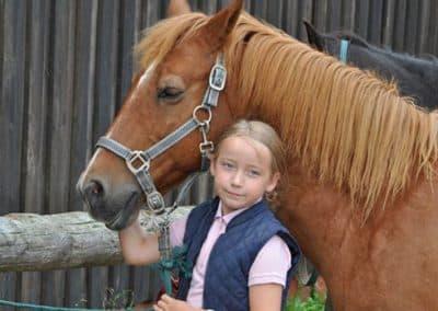Ein blondes Mädchen mit blauer Weste, hält den Kopf eines braunen Pferdes fest, während sie einen Tag auf dem Reiterhof Pferdeschulze verbringt