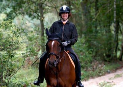 Eine Frau auf ihrem Pferd reitet auf dem Waldweg in der Lüneburger Heide