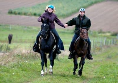 2 Reiter halten sich während des Erlebnisreiten im Galopp die Hände