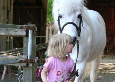 Blondes Mädchen führt ein Pony an den Zügeln vor dem Stall des Landhotels Pferdeschulze