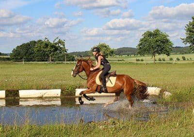 Frau mit Pferd galoppiert durch die Wasserfurt auf dem Geländeplatz.