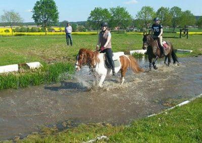 Zwei Mädchen mit ihren Ponys reiten durch eine Wasserfurt auf dem Geländeplatz.
