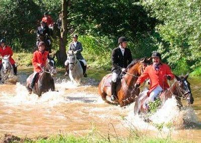 Jagdreiter reiten mit ihren Pferden durch einen Fluss