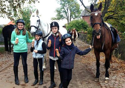 Vier Kinder stehen mit einem Eis in der Hand vor einem weißen und einem Braunen Pferd, während eines Ausflugs mit dem Landhotel Pferdeschulze