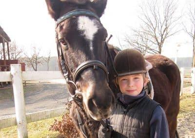 Ein jugendlicher Junge hält sein dunkelbraunes Pferd mit weißer an den Zügeln, auf dem Reiterhof des Landhotels Pferdeschulze