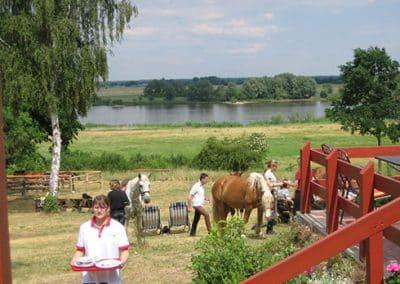 EIne Frau mit Geschirr und im Hintergrund Reiter mit ihren Pferden neben der Terrasse vom Landhotel Pferdeschulze