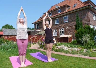 Zwei Frauen praktizieren Yoga im Garten.