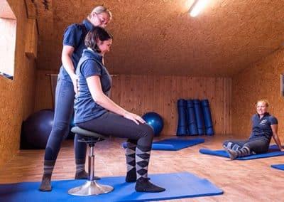 Yogalehrerin zeigt Übungen für Reiter.