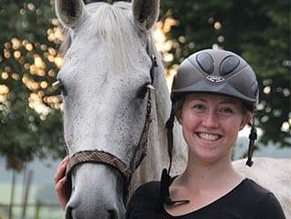 Glückliche Reiterin mit Pferd im Veganurlaub