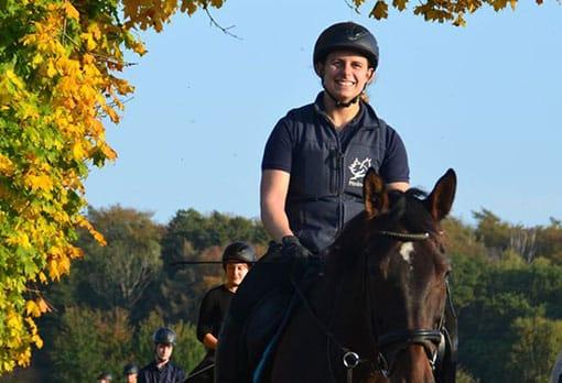 Erwachsene, lächelnde Frau auf ihrem Pferd führt eine Schlange von mehreren Reitern an