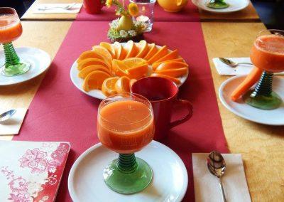 Ein gedeckter Tisch mit Geschnittene Orangen und frisch gepresster Gemüsesaft
