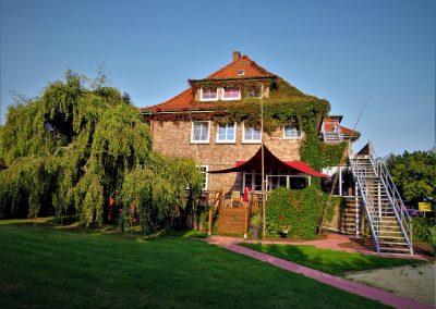 Ein Landhotel mit einem Sonnensegel über der Holzterrasse
