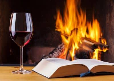Ein volles Rotweinglas und ein augeschlagenes Buch vor einem Brennenden Feuer