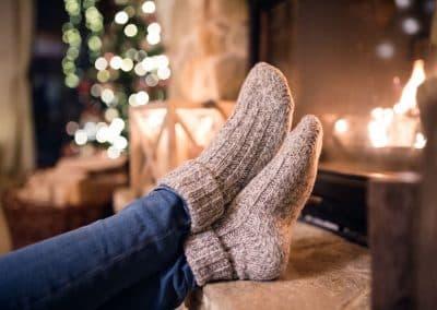 Hochgelegte Füße in Baumwollsocken vo einem brennenden Kamin